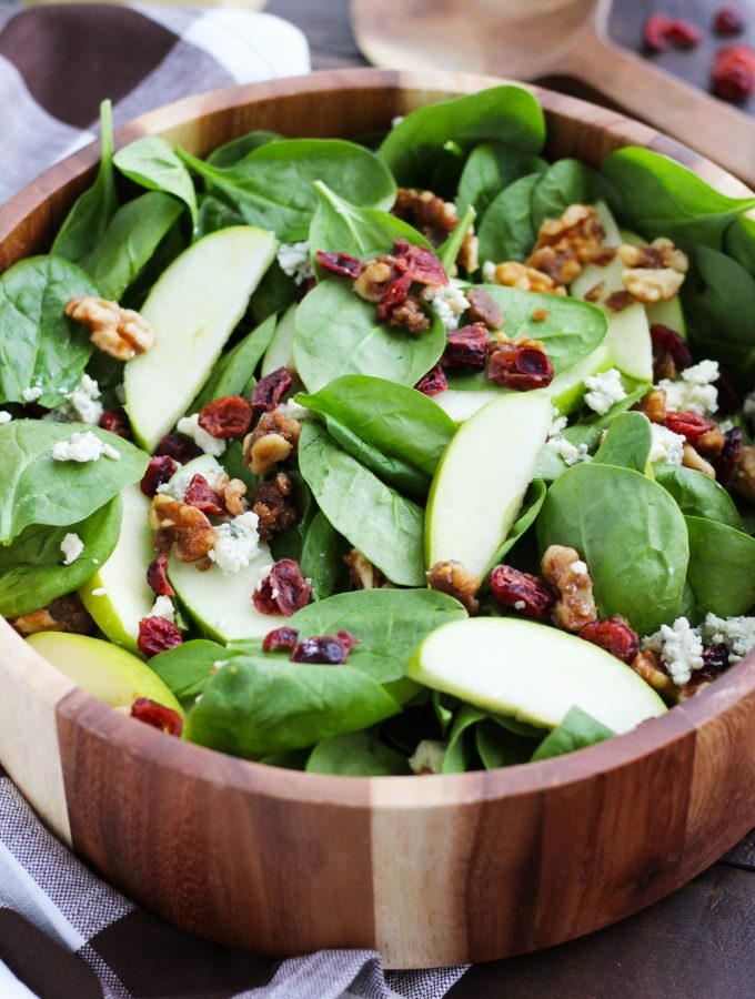 This Apple Cranberry Spinach Salad with Candied Walnuts is the perfect holiday side dish or easy meal with the addition of chicken.   It gets topped with blue cheese crumbles and a homemade, Creamy Apple Cider Vinaigrette dressing