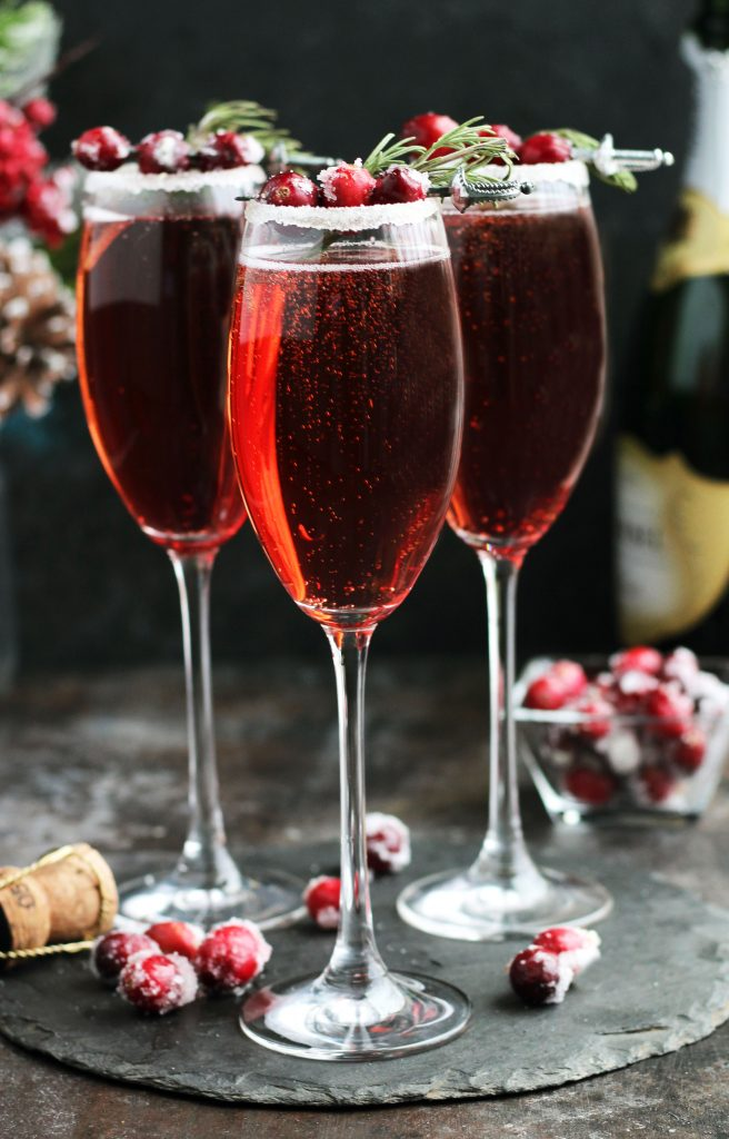 These Cranberry Mimosas with orange liqueur, champagne and cranberry juice are perfect for holiday entertaining.  A sugared rim with rosemary and sugared cranberries makes this cocktail colorful and festive.