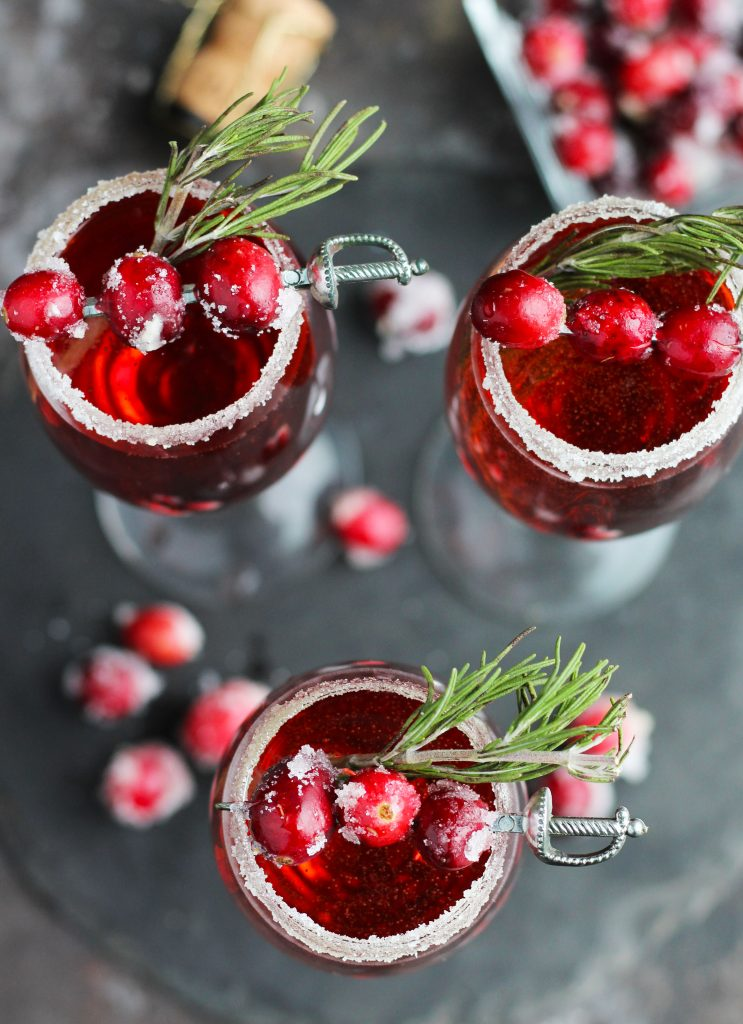 This Cranberry Mimosa gets orange liqueur and is topped with sugared cranberries and rosemary for a festive, holiday cocktail.