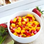 This Strawberry Mango Salsa with Cinnamon Tortilla Chips is simple to make and the perfect, refreshing summertime appetizer.  Fresh strawberries and mangoes get added to this flavorful salsa with a touch of lime juice and mint.  Tortillas get brushed with melted butter, sprinkled with cinnamon and sugar, and cut into triangles before baking into a crispy chip.