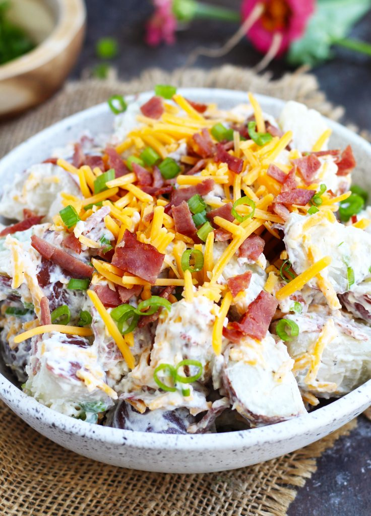 This Loaded Potato Salad is a great, easy side dish for your summer barbecues. It tastes like biting into a potato skin with a sour cream and ranch dressing mixture with a bacon, cheddar cheese and green onion topping.