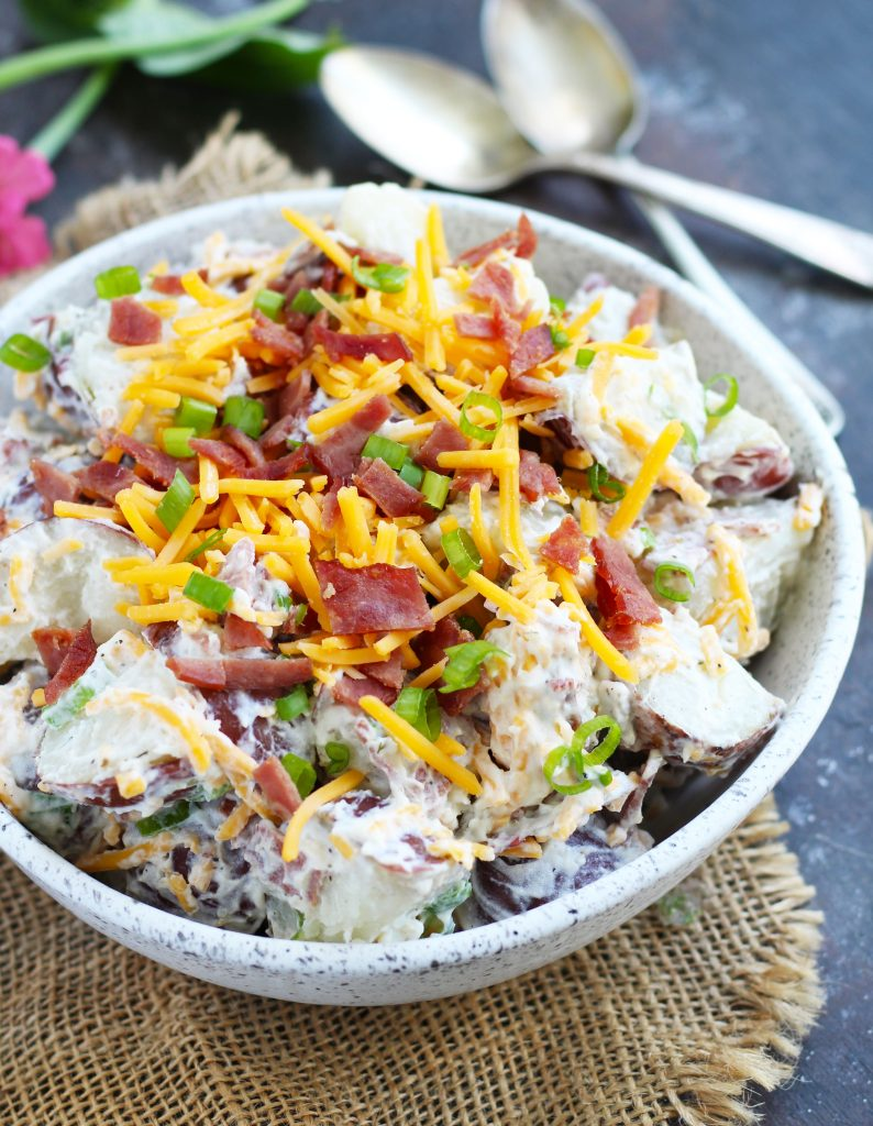 This Loaded Potato Salad is a great, easy side dish for your summer barbecues. It tastes like biting into a potato skin with a sour cream and ranch dressing mixture and that coveted bacon, cheddar cheese and green onion topping.