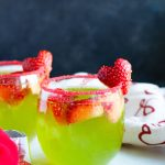This Grinch Sangria with Pinot Grigio, Midori and pineapple juice is a sweet addition to your Christmas menu. A red sugar sprinkle rim and a small strawberry heart cut-out make this gorgeous cocktail festive for the holidays.